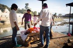 在火葬仪式期间的当地人沿圣洁巴格马蒂河在Pashupatinath寺庙的Bhasmeshvar Ghat在加德满都 图库摄影