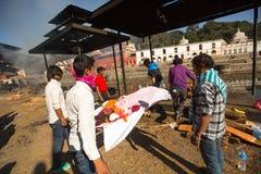 在火葬仪式期间的未认出的当地人沿圣洁巴格马蒂河在Bhasmeshvar Ghat 免版税库存照片