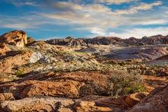 在火谷的岩石风景与多云日落的 库存照片