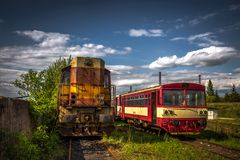 在火车公墓在夏天与绿草和树的老内燃机车在背景和伟大的多云天空中 免版税库存图片