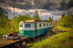 在火车公墓在夏天与绿草和树的老机车在背景和伟大的多云天空中 免版税库存照片