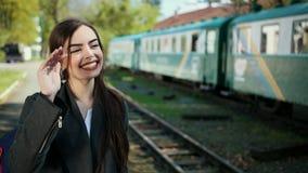 在火车支架前面的一个美好和愉快的女孩身分在她的手上有一张票并且向她说再见 股票录像