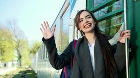 在火车支架前面的一个美好和愉快的女孩身分在她的手上有一张票并且向她说再见 股票视频