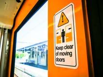 在火车的Keep clear of移动的门标志 免版税库存图片