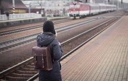 在火车站平台的少妇等待的火车  免版税库存图片