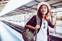 在火车站的少妇旅客佩带的背包等待的铁路 免版税库存图片
