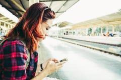 在火车站的少妇旅客佩带的背包等待的铁路 图库摄影