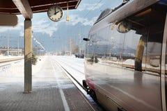 在火车站的时钟和培训 免版税库存图片