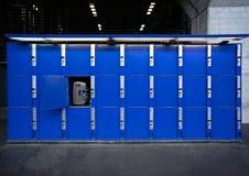 在火车站的蓝色大衣物柜的袋子或手提箱 免版税库存照片
