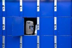 在火车站的蓝色大衣物柜的袋子或手提箱 库存照片