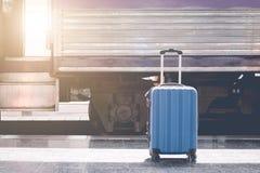 在火车站的蓝色手提箱与在减速火箭的抽象光 库存照片