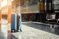 在火车站的蓝色手提箱与在减速火箭的抽象光 免版税库存照片