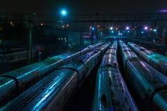 在火车站的许多火车在晚上 免版税图库摄影