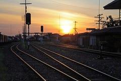 在火车站的铁路轨道在日落期间 免版税图库摄影