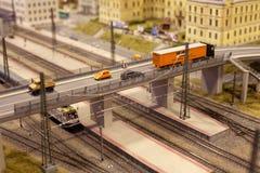 在火车路轨的桥梁在有卡车和汽车的城市在微型世界 库存照片