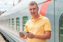在火车附近供以人员拿着片剂计算机 图库摄影