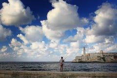 在灯塔前面的男孩渔 免版税库存图片