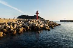 在灯塔的人观看的日落在与wavebreakers的一座防波堤在西归浦,济州海岛,韩国 免版税库存照片