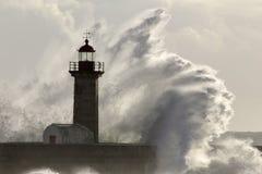 在灯塔的大风雨如磐的海波浪飞溅 免版税库存图片