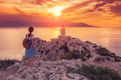 在灯塔的美好的日落在Loutraki,希腊的Melagavi海角 免版税图库摄影