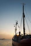 在灯塔船后的日落 库存图片