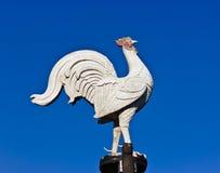 鸡雕象在蓝天blackground的石头白色 免版税库存图片