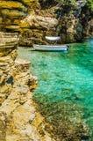 在灰岩峭壁围拢的小逗人喜爱的天蓝色的海湾的白色小船在科孚岛海岛,希腊 免版税库存照片