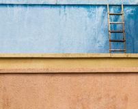 在灰泥的老木梯子 免版税库存图片