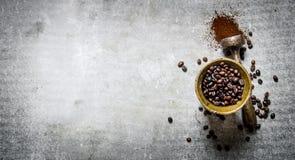 在灰浆的烤咖啡豆与杵 免版税库存图片