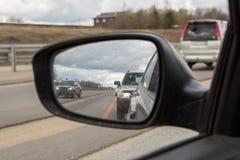 在灰色云彩下的路在汽车镜子 库存图片