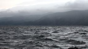 在灰色云彩背景的风暴在天空和贝加尔湖中黑黑暗的水  影视素材