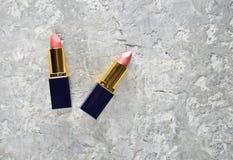 在灰色具体背景的两支桃红色唇膏 库存照片