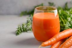 在灰色具体背景的新鲜的红萝卜汁 库存图片