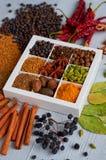 在灰色厨房用桌上的香料:八角,芬芳胡椒,桂香,肉豆蔻,海湾离开,辣椒粉接近  香料纹理 免版税库存照片