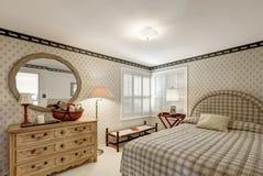 在灰色口气的舒适卧室设计以米黄草裱糊的墙壁为特色 免版税图库摄影
