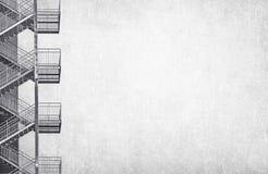 在灰色困厄的墙壁背景的金属工业楼梯 库存图片