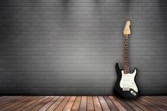 在灰色墙壁上的吉他 库存图片