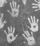 在灰色墙壁上的白色油漆handprints 免版税库存照片