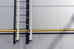在灰色墙壁和黄色管上的梯子 图库摄影