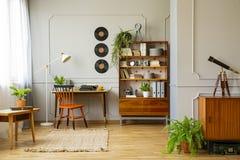 在灰色墙壁有铸造的和木家具上的唱片装饰在作家的减速火箭的家庭办公室内部 真正的phot 免版税库存照片