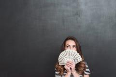 在灰色墙壁的小姐在手上的拿着金钱 图库摄影