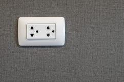 在灰色墙壁背景的电子插座 图库摄影
