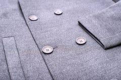 在灰色外套的按钮 免版税库存照片