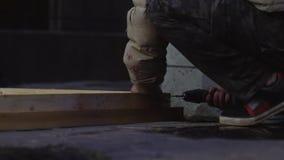 在灰色夹克的人的手使用电子螺丝刀连接板条 股票录像