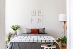 在灰色床上的海报与在卧室interio的被仿造的毯子 免版税库存图片