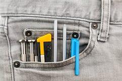 在灰色斜纹布口袋的工具 免版税库存照片