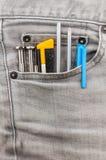 在灰色斜纹布口袋的工具 库存照片