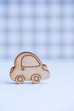 在灰色方格的背景的木汽车象 免版税库存图片