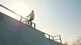 在灰色有冠乌鸦身分的一个专业BMX车手在与他的自行车,然后去的上面下坡 股票视频