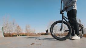 在灰色有冠乌鸦骑马的一个bmx车手在skatepark和曲柄方向盘 股票录像